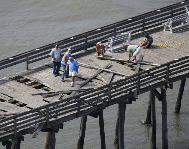 Workers begin repairs on the Virginia Beach fishing pier a day after Hurricane Irene came through the area in Virginia Beach, Va., Sunday, Aug. 28, 2011. The storm killed at least 14 people and left 4