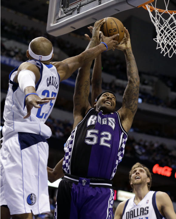 Dallas Mavericks' Vince Carter (25) tries to block Sacramento Kings' James Johnson (52) as he goes up to score in the first half of an NBA basketball game as the Mavericks' Dirk Nowitzki, bottom right