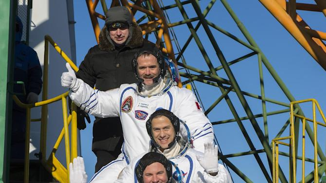 Expedition 34 NASA Flight Engineer Chris Hadfield of the Canadian Space Agency (CSA), top, NASA Flight Engineer Tom Marshburn and Soyuz Commander Roman Romanenko of Russia wave farewell from the bottom of the Soyuz rocket at the Baikonur Cosmodrome in Baikonur, Kazakhstan, Wednesday, Dec. 19, 2012.  Marshburn, Romanenko and  Hadfield will travel for two days in the capsule, before docking with the space station where three other astronauts are already on board.  (AP Photo/NASA, Carla Cioffi)