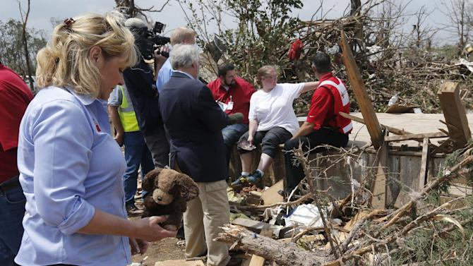 Oklahoma Gov. Mary Fallin, left, picks up a stuffed dog from the rubble of Kimberly Graham's home, at the Steelman Estates Mobile Home Park, which was hard hit in Sunday's tornado, near Shawnee, Okla., Monday, May 20, 2013. Graham is seated at rear in white talking with Red Cross workers. (AP Photo Sue Ogrocki)