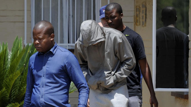 Olympic athlete Oscar Pistorius, center. leaves the Boschkop police station, east of Pretoria, South Africa, Thursday, Feb. 14, 2013 en route to appear in court charged with murder.  Olympic athlete Oscar Pistorius was taken into custody and was expected to appear in court Thursday after a 30-year-old woman who was believed to be his girlfriend was shot dead at his home in South Africa's capital, Pretoria. (AP Photo/Chris Collingridge) SOUTH AFRICA OUT