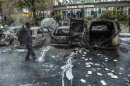 A bystander checks the debris around a row of burnt cars in the suburb of Rinkeby after youths rioted in several different suburbs around Stockholm