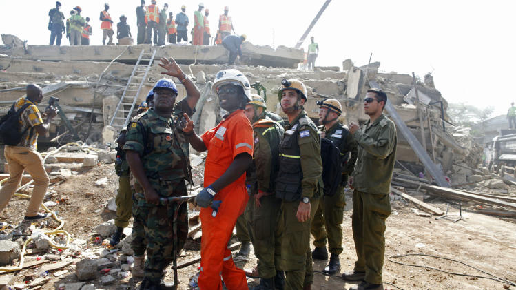 A member of the Israeli forces , right, liaise with local authorities as they assist in the Ghana relief efforts to find survivors, after a building collapsed in Accra, Ghana, Thursday, Nov. 8, 2012.  Authorities on Thursday blamed faulty construction for the collapse of the five-storey building in Ghana's capital that killed at least nine people and trapped some dozens of others as search and rescue efforts continue Thursday.  (AP Photo/Gabriela Barnuevo)