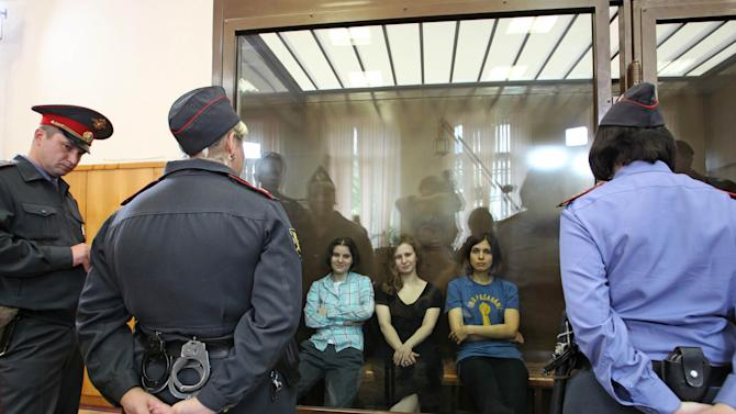 "Feminist punk group Pussy Riot members, from left, Yekaterina Samutsevich, Maria Alekhina and Nadezhda Tolokonnikova sit in a glass cage at a court room in Moscow, Russia on Friday, Aug 17, 2012. The women, two of whom have young children, are charged with hooliganism connected to religious hatred but the case is widely seen as a warning that authorities will only tolerate opposition under tightly controlled conditions. T-shirt on right worn by Tolokonnikova is Spanish and translates to ""They shall not pass"", a slogan often used to express determination to defend a position against an enemy. (AP Photo/Mikhail Metzel)"