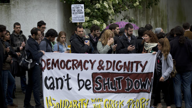 "Supporters of ERT, the Greek state-run TV and radio company, hold up a banner for it to be photographed as they take part in a protest outside the Greek embassy in London, Wednesday, June 12, 2013.  Greece's conservative-led government was facing a political crisis Wednesday after its decision to shut down state-run TV and radio triggered a wave of strikes and fierce opposition from within the coalition government. TV and radio signals from the Hellenic Broadcasting Corp., or ERT, went dead early Wednesday, hours after the government closed the broadcaster down and fired its 2,500 workers, citing the need to cut ""incredible waste"".  (AP Photo/Matt Dunham)"