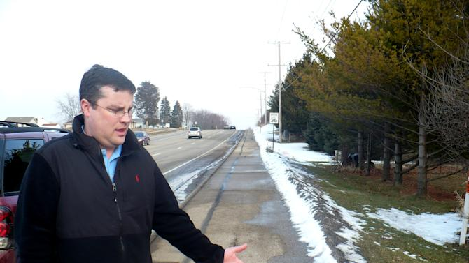 Mike Vega points to the area of sidewalk in Madison, Wis., Wednesday, Feb. 15, 2012, where he discovered a starving 15-year-old after she escaped from her abusive father and stepmother last week. The severely malnourished teenager had been forced to stay in an unfinished basement for years and an alarm would sound if she went upstairs, police records say. The teen told authorities she ate what she could find in the garbage and on the floor of her father and stepmother's Madison home. Sometimes she was made to eat her feces and drink her own urine, according to a police affidavit. (AP Photo/Todd Richmond)