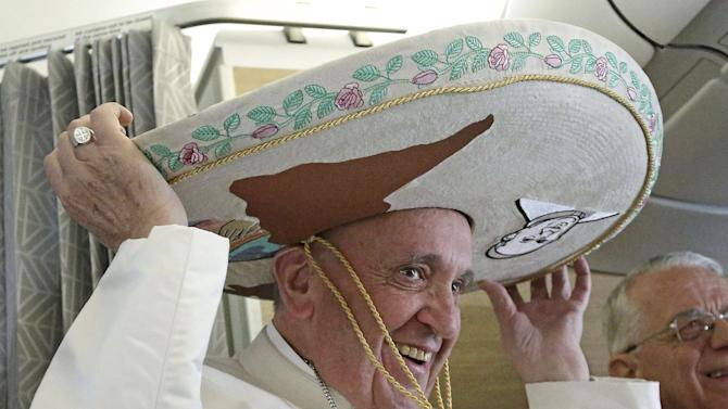 Pope Francis wears a Sombrero hat he received as a gift by a Mexican journalist aboard of the airplane to Habana