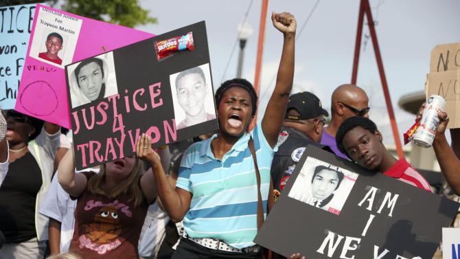 Protestors, Lakesha Hall, 32, of Sanford, center, and her son, Calvin Simms, 12, right, gather early for a rally for Trayvon Martin, the black teenager who was fatally shot by a neighborhood watch captain last month, at Fort Mellon Park in Sanford, Fla., Thursday, March 22, 2012. (AP Photo/Julie Fletcher)