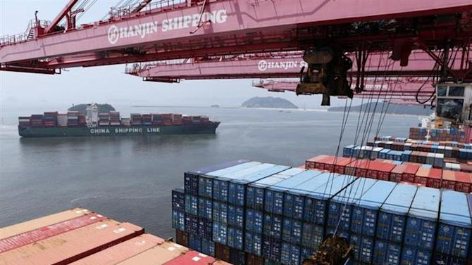 A crane carries a container from a Hanjin Shipping ship at the Hanjin container terminal as a China Shipping Line ship (L) arrives at the Busan New Port in Busan, about 420 km (261 miles) southeast of Seoul, August 8, 2013.