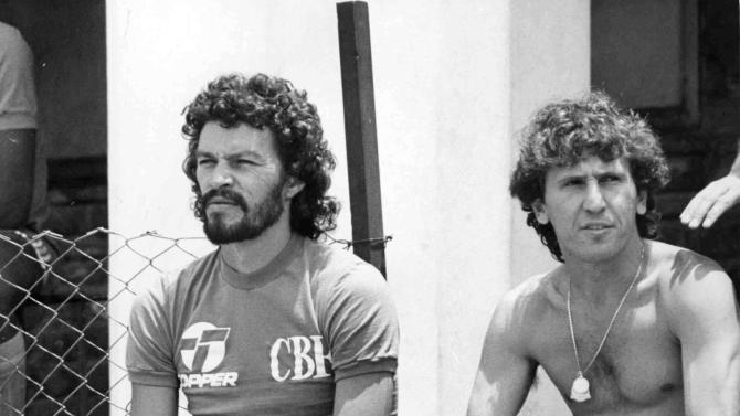 FILE.- This May 18, 1986 file photo show Brazilian soccer players Socrates, left, and Zico, relax on a wall while watching their teammates playing a friendly match against some local players on a ground near Azteca Stadium, Mexico City, on May 18, 1986. After, on Saturday, the Albert Einstein hospital released a statement saying Socrates was back in the hospital and on life support, suffering from septic shock resulting from an intestinal infection, Brazilian media reported early Sunday Socrates, a former Brazil World Cup captain, has died in hospital aged 57. (AP Photo/Nick Ut, file)