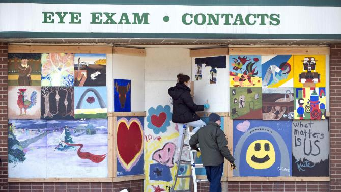 Rachel Cofer and Kevin Conway paint a mural on a boarded up store in Ferguson