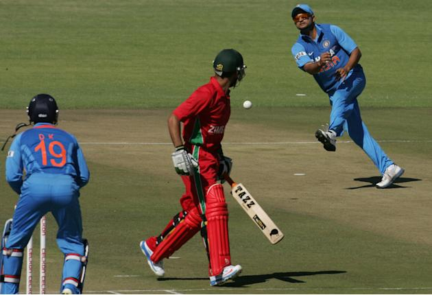 Indian fielder Suresh Raina attempts a run-out against Raza Butt of Zimbabwe as wicket keeper Dinesh Kathik looks on during the first of the five ODI cricket series matches between India and hosts Zim