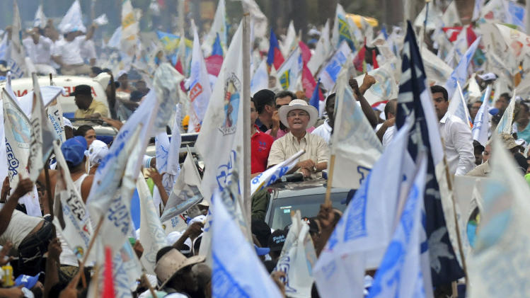 Former president and candidate for the opposition Dominican Revolutionary Party Hipolito Mejia, center, arrives to his closing campaign rally in Santo Domingo, Dominican Republic, Friday, May 18, 2012. Dominicans will go the polls to elect a new president on Sunday. (AP Photo/Manuel Diaz)