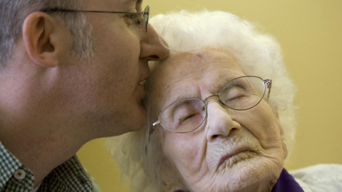 FILE - In this March 10, 2011 file photo, Besse Cooper, 114, right, receives a kiss from her grandson Paul Cooper, 42, during a ceremony in which Guinness World Records recognizes her as the word's oldest living person, at the nursing home where she lives in Monroe, Ga. Besse Cooper, the woman who was listed as the world's oldest person has died Tuesday, Dec. 4, 2012 in a Georgia nursing home at age 116, according to her son Sidney Cooper. (AP Photo/John Amis, File)