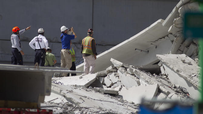 Rescue officials survey damage in the collapsed parking garage at the Miami Dade College West campus in Doral, Fla. Thursday, Oct. 11, 2012. One person is still missing. (AP Photo/J Pat Carter)