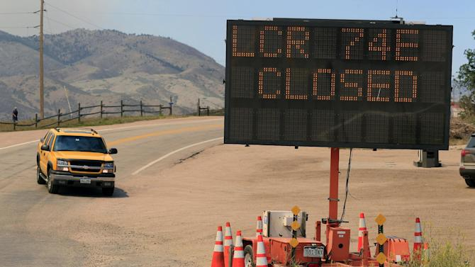 A pickup truck makes its way down Larimer County Highway 74W past a road closure sign as a wildfire continues to burn near Livermore, Colo., on Saturday, June 23, 2012. Authorities sent out 992 evacuation notices Friday due to the wildfire burning on more than 100 square miles in northern Colorado as winds pick up. (AP Photo/David Zalubowski)