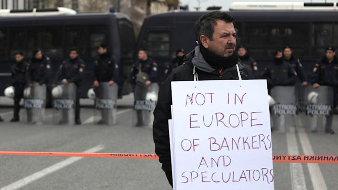 An employee at the state-run Workers' Housing Organization, OEK, holds a banner in front of riot police during a protest in central Athens, Wednesday, Feb. 29, 2012. Late Tuesday, parliament approved new cuts in public sector pensions and government spending required to secure a second package of international rescue loans, while the Cabinet formally imposed deep cuts to the minimum wage, retroactively to Feb. 14. (AP Photo/Petros Giannakouris)