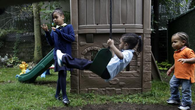 Malayasia Blackwood, 7, left, her brother Omarhie Blackwood, 1, right, and Rihanna Hall, 3, play in the yard of the Drew House in New York, Wednesday, Oct. 3, 2012.  The program, called Drew House, is one of a kind in the nation, where mothers arrested on felonies can live with their children, instead of in prison. The program has been lauded as a success that should be replicated around the country, but the small house is already full, and without additional funding and space, it can't grow.  (AP Photo/Seth Wenig)