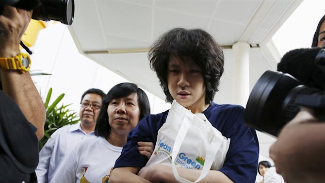 Teen blogger Amos Yee leaves with his parents after his sentencing, from the State Courts in Singapore