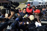 <p>Venezuelan President Hugo Chavez (C) speaks to the press in Punto Fijo, Venezuela, a day after a massive blast at the country's largest oil refinery. The devastating fire triggered by an explosion was still burning strong Sunday, as the toll jumped to 41 and the country was in national mourning.</p>