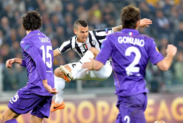 Juventus forward Sebastian Giovinco, center, is airborne as Fiorentina's Stefan Savic, left, and Gonzalo look at him, during an Europa League, round of 16, soccer match between Juventus and Fioren