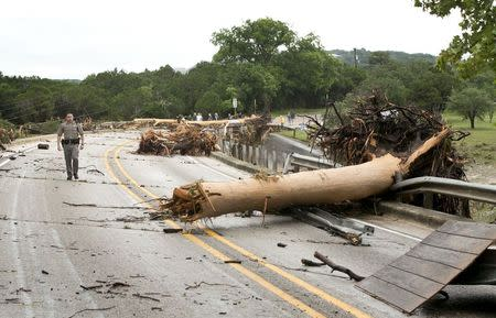 Trooper Marcus Gonzales walks on the Highway 12 bridge over the Blanco River which was blocked by large trees after flooding in Wimberly, Texas