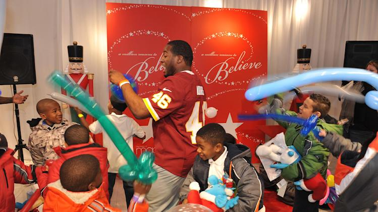 "IMAGE DISTRIBUTED FOR MACY'S - In this image released on Wednesday, Dec. 12, 2012, Alfred Morris entertains children with their balloon swords at the Macy's ""Covered for the Holidays"" event in Washington, DC. Macy's and the Washington Redskins hosted the annual ""Covered for the Holidays"" event at Metro Center for 300 local underserved children. (Larry French/AP Images for Macy's)"