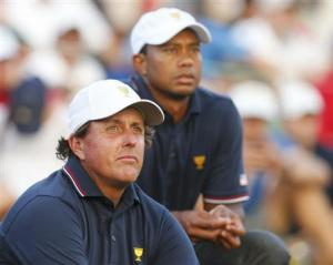 U.S. teammates Tiger Woods and Phil Mickelson watch play after finishing their matches during the opening Four-ball matches for the 2013 Presidents Cup golf tournament at Muirfield Village Golf Club in Dublin