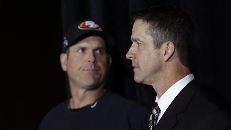 Brothers Jim Harbaugh, left, head coach for the San Francisco 49ers, and John Harbaugh, head coach for the Baltimore Ravens, arrive at a news conference for the upcoming Super Bowl XLVII in New Orleans, Friday, Feb. 1, 2013. (AP Photo/Gerald Herbert)