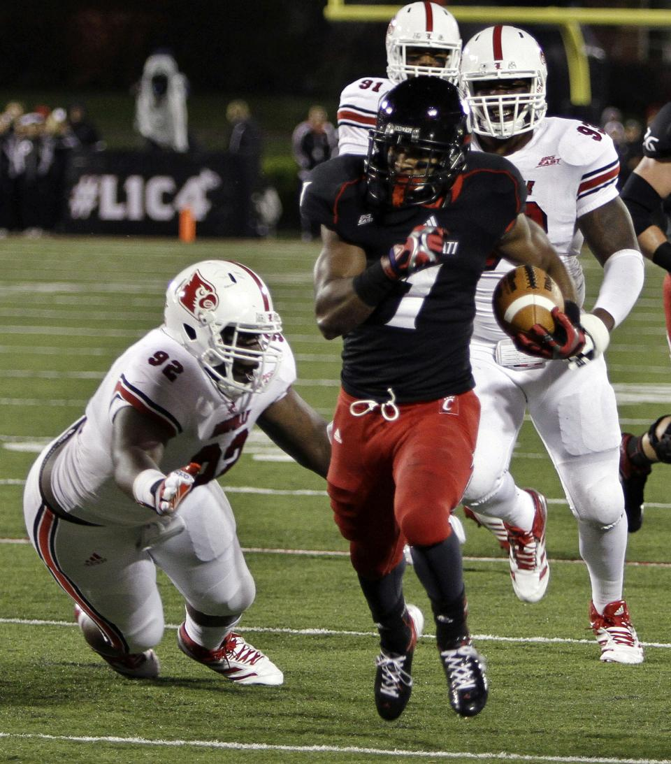 Cincinnati running back Ralph David Abernathy (1) sprints away from Louisville's Brandon Dunn (92) and Roy Philon (93) to score on a 14-yard run during the first quarter of an NCAA college football game in Louisville, Ky., Friday, Oct. 26, 2012. (AP Photo/Garry Jones)