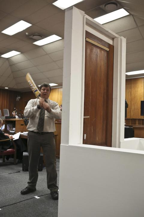 A policeman demonstrates effect of hitting bathroom door with cricket bat during trial of Oscar Pistorius in North Gauteng High Court in Pretoria