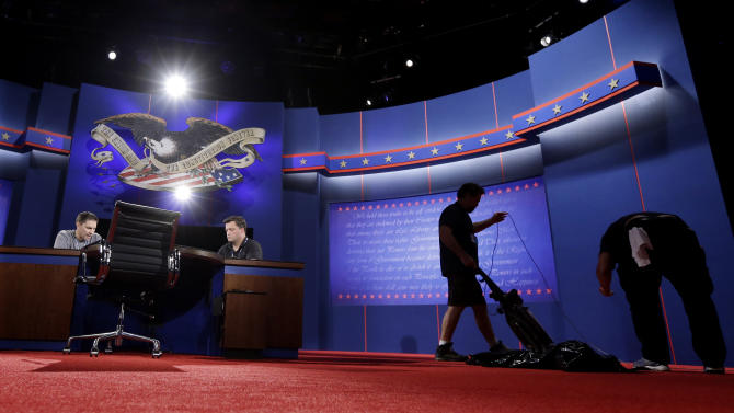 Workers prepare the set for Monday's presidential debate, Sunday, Oct. 21, 2012, in Boca Raton, Fls.  President Barack Obama and Republican presidential candidate and former Massachusetts Gov. Mitt Romney will hold their final debate Monday. (AP Photo/Eric Gay)