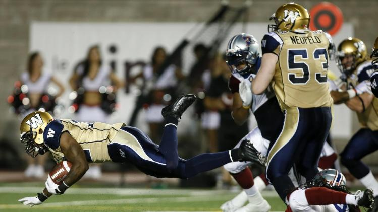 Winnipeg Blue Bombers Grigsby is tackled by Montreal Alouettes Brown during CFL football action in Montreal