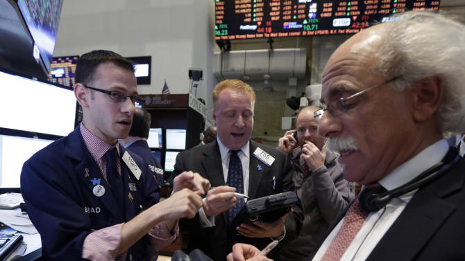 FILE - Specialist Bradley Kessler, left, works with traders on the floor of the New York Stock Exchange in this May 7, 2013 file photo. Financial markets were subdued Thursday May 16, 2013 despite encouraging growth figures out of Japan, as investors paused for breath a day after the main U.S. stock indexes struck record highs. (AP Photo/Richard Drew, File)