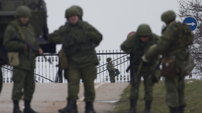 Unidentified gunmen wearing camouflage uniforms guard the entrance to the military airport at the Black Sea port of Sevastopol in Crimea, Ukraine, Friday, Feb. 28, 2014. Russian troops took control of the two main airports in the strategic peninsula of Crimea, Ukraine's interior minister charged Friday, as the country asked the U.N. Security Council to intervene in the escalating conflict. Russian state media said Russian forces in Crimea denied involvement. No violence was reported at the civilian airport in Crimea's capital of Simferopol or at the military airport in the Black Sea port of Sevastopol, also part of Crimea. At the Simferopol airport, a man claiming to speak for the camouflage-clad forces patrolling the airport described them as Crimean militiamen. (AP Photo/Ivan Sekretarev)