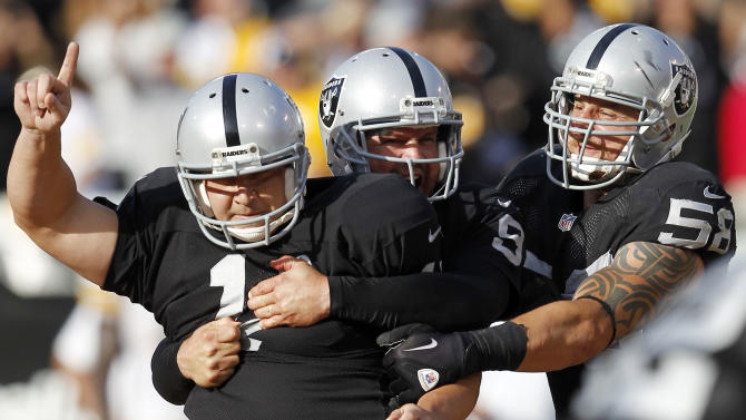 Oakland Raiders kicker Sebastian Janikowski  (11) celebrates with holder Shane Lechler (9) and  Dave Tollefson (58) after Janikowski's 43-yard field goal to win the game against the Pittsburgh Steelers during the fourth quarter of an NFL football game in Oakland, Calif., Sunday, Sept. 23, 2012. The Raiders won 34-31. (AP Photo/Tony Avelar)