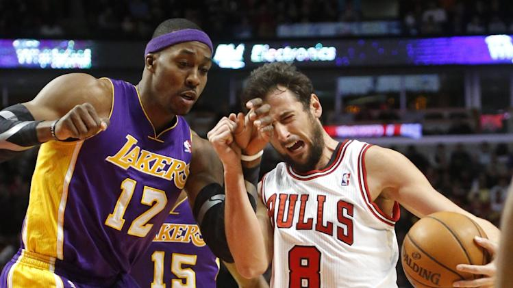 Los Angeles Lakers center Dwight Howard (12) fouls Chicago Bulls guard Marco Belinelli during the second half of an NBA basketball game Monday, Jan. 21, 2013, in Chicago. The Bulls won 95-83. (AP Photo/Charles Rex Arbogast)