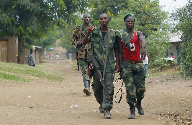 FILE - In this Aug. 5, 2012 file photo, M23 rebel fighters walk through the streets of Kiwanja 80 kilometers (50 miles) north of Goma, Congo. A Rwandan-backed rebel group advanced to within 3 kilomete