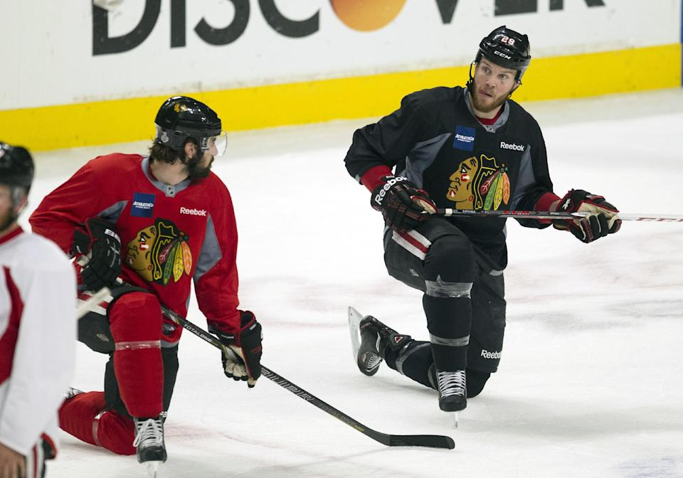 Chicago Blackhawks defenseman Nick Leddy, left, looks over to left wing Bryan Bickell during NHL hockey practice Friday, June 14, 2013, in Chicago. The Blackhawks lead the Boston Bruins 1-0 in the best-of-seven games Stanley Cup final series. Game 2 is scheduled for Saturday in Chicago.  (AP Photo/Scott Eisen)