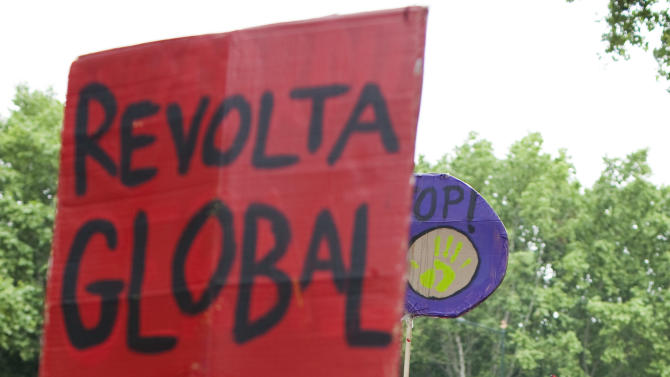 """A woman shouts slogans while another holds a sign with the words """"Global Revolt"""" during an anti-austerity protest in Lisbon Saturday, May 12 2012. Hundreds took part in the demonstration organized to coincide with dozens of others being held around the globe. (AP Photo/Armando Franca)"""