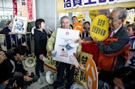 Demonstrators hold a placard showing a portrait of Hong Kong chief executive Leung Chun-ying as they protest prior to his his policy address on January 16, 2013. Hong Kong's Beijing-backed leader has unveiled a raft of populist policies with an emphasis on tackling the city's housing crisis, as he aimed to hush critics' repeated calls to step down
