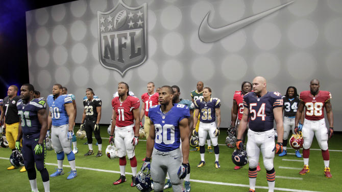 NFL players stand in their new uniforms during a presentation in New York, Tuesday, April 3, 2012. The league and Nike showed off the new look in grand style with a gridiron-styled fashion show at a Brooklyn film studio. (AP Photo/Seth Wenig)