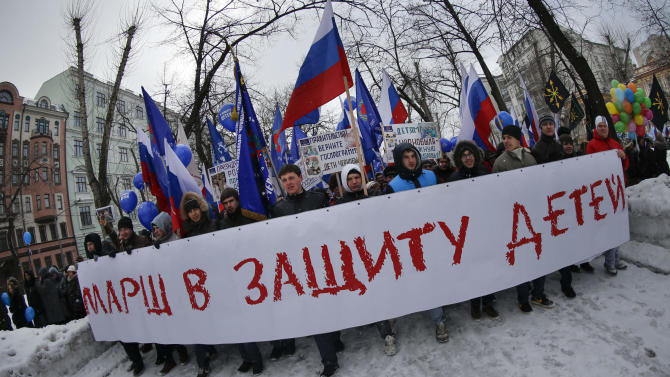 "Demonstrators carry Russian flags and a huge poster reading ""March in Defense of Children"" during a massive rally in Moscow, Saturday, March 2, 2013. Russia voiced strong skepticism Saturday about the U.S. autopsy on Max Shatto, a 3-year-old adopted Russian boy in Texas and demanded further investigation as thousands rallied in Moscow to support the Kremlin ban on U.S. adoptions of Russian children. (AP Photo/Alexander Zemlianichenko)"