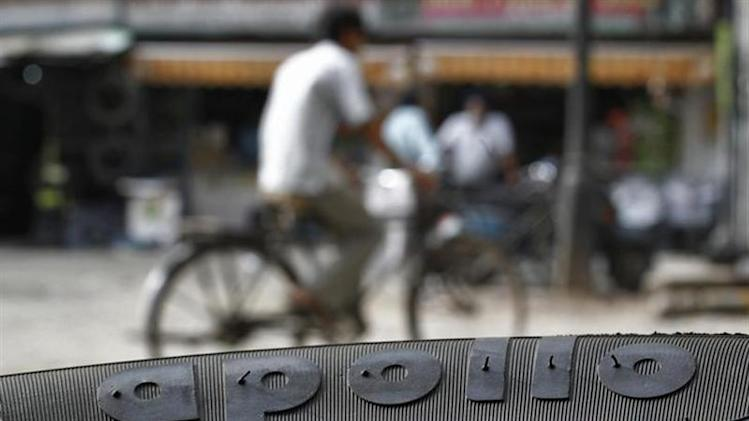 A cyclist rides past an Apollo tyre kept on display at a multi-brand tyre showroom in New Delhi June 13, 2013. REUTERS/Anindito Mukherjee