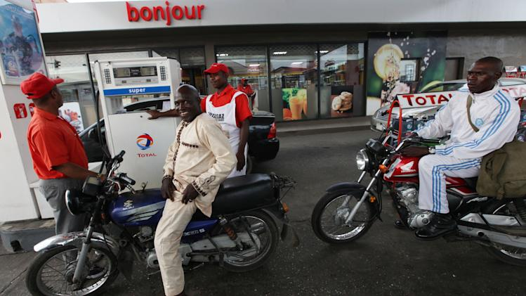 A petrol attendant sells fuel  to motorcycle taxis at a Total petrol station in Lagos, Nigeria, Monday, Nov. 19, 2012. French oil company Total SA said Monday it had sold its stake in an offshore oil field near Nigeria for $2.5 billion to the Chinese state-run firm Sinopec Corp., a sign of the China's growing stakes in the West African nation's oil production. (AP Photo/Sunday Alamba)