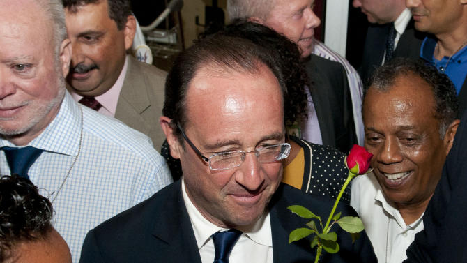 Socialist presidential candidate Francois Hollande holds a rose as he arrives at Saint-Denis de la Reunion airport in La Reunion island, Saturday, March, 31, 2012. Hollande is on a two-day campaign visit to the French island in the Indian Ocean. (AP Photo/Fabrice Wislez)