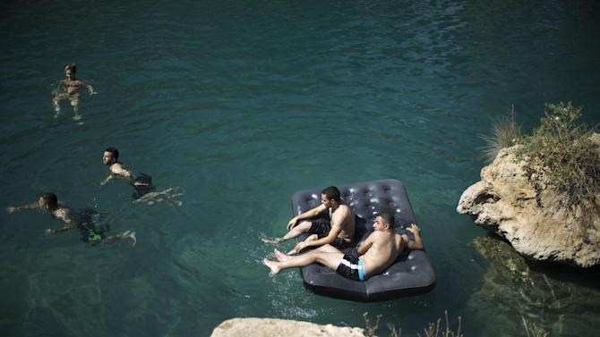 People cool off as they bathe at the Gan HaShlosha national park near the northern Israeli Town of Beit Shean on Thursday, July 30, 2015. The temperature there reached 37 degrees Celsius (98.6 F). (AP Photo/Ariel Schalit)