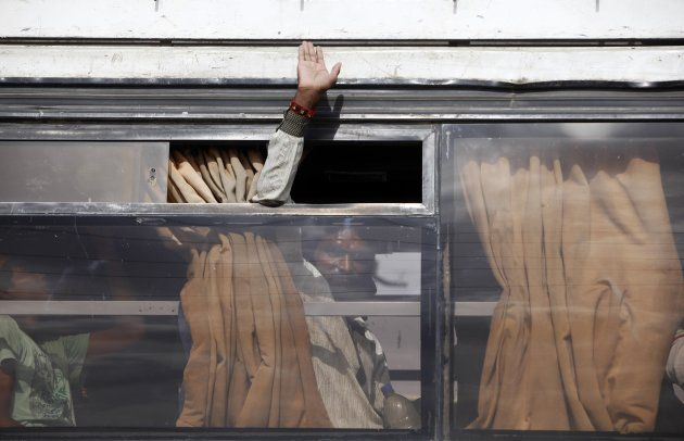 A fisherman from India waves from the window of a bus after his release from a prison in Karachi
