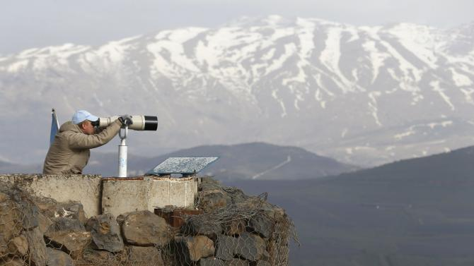 A member of UNDOF looks through binoculars at Mount Bental in the Golan Heights