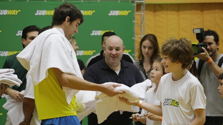 Former U.S. Olympic Swimmer Michael Phelps gives towels for the children at Competition academy, during a event organized by SUBWAY restaurants, on Wednesday, Dec. 4, 2013 in Sao Paulo, Brazil. (Photo by Nelson Antoine/Invision for SUBWAY Restaurants/AP Images)